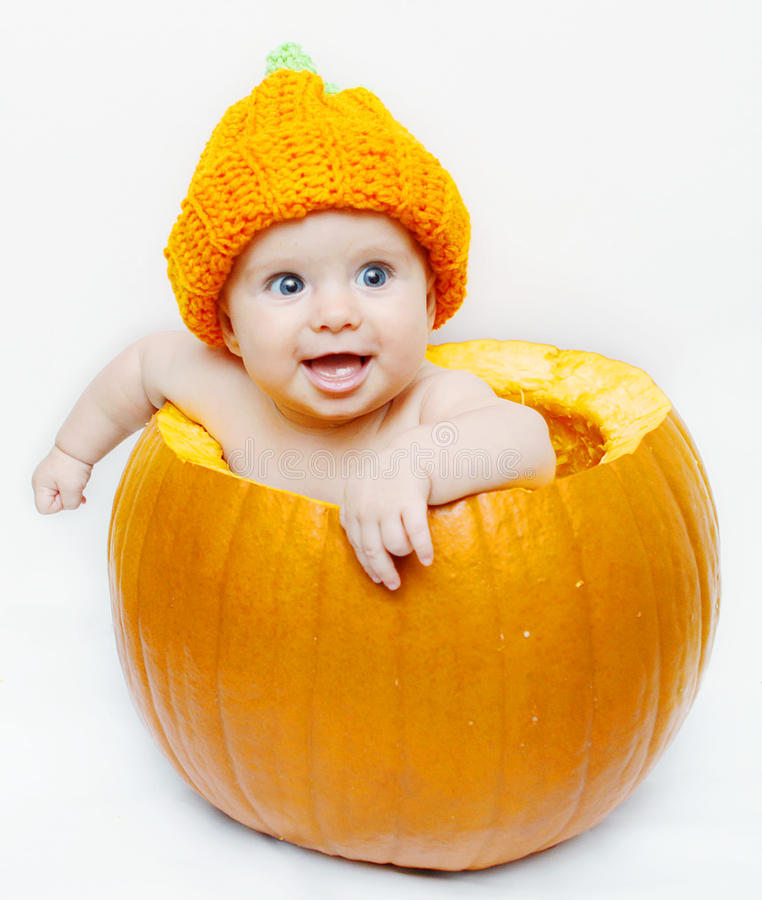 Happy baby in a pumpkin. Sweet cute happy baby in a pumpkin royalty free stock photography