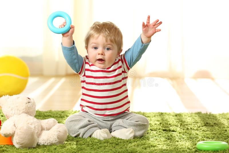 Happy baby raising arms with a toy on the floor royalty free stock photography