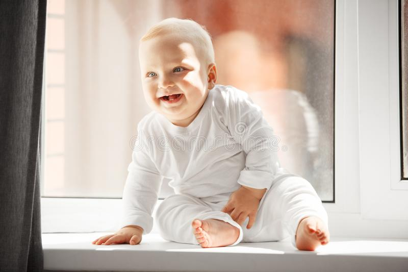 Happy baby that sits and laughs on windowsill. Happy baby with big light eyes, funny smile and blond hair dressed in white crawlers sits and laughs on spacious royalty free stock image