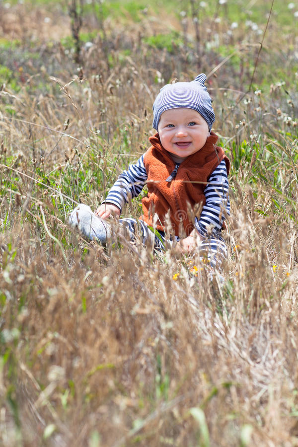 Happy baby sitting in the grass stock photo