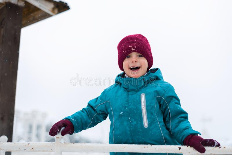 Happy baby smiling. boy plays in the winter in the playground. the child is wearing a red hat, blue jacket and mittens royalty free stock images