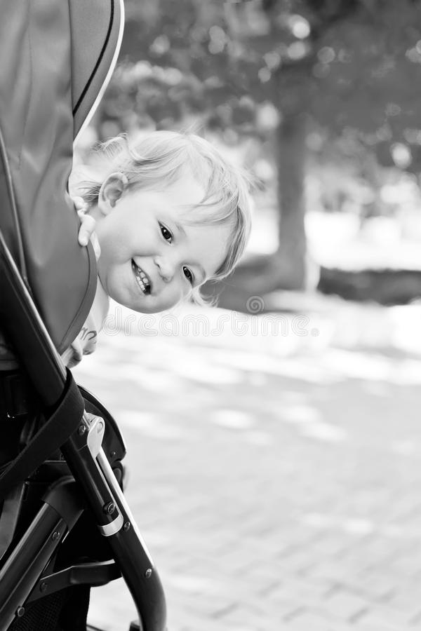 Happy baby in a stroller. Looks out laughing in the park ( black and white royalty free stock image