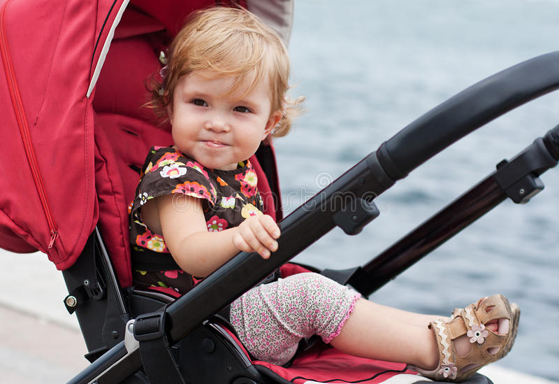 Happy baby in a stroller. Smiling baby in a stroller in the background of the sea stock images