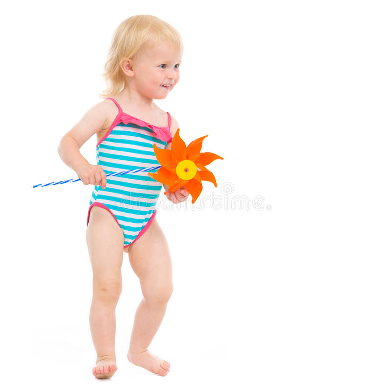 Happy baby in swimsuit with pinwheel. Looking on copy space stock photos