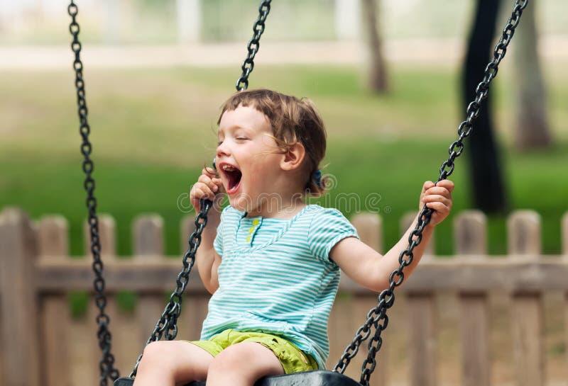 Happy baby on swing stock photography