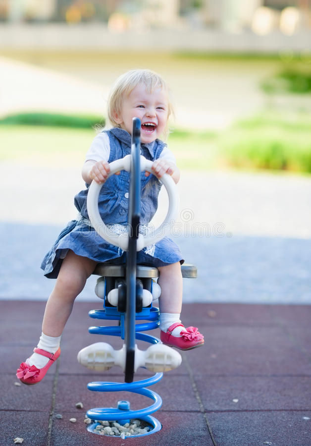 Download Happy Baby Swinging On Horse On Playground Stock Image - Image: 25260889