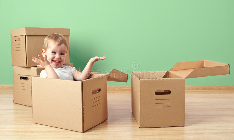 Happy baby toddler sitting in a cardboard box. Empty room