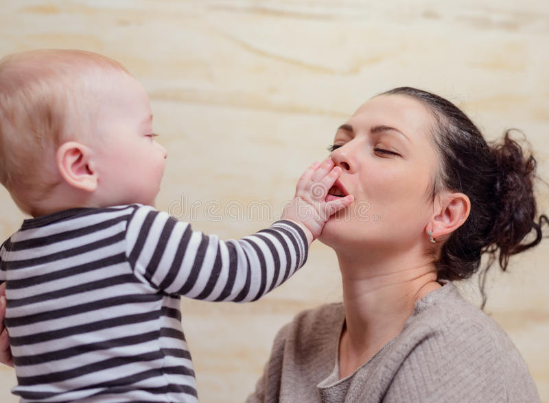 Happy baby touching face of woman stock photos