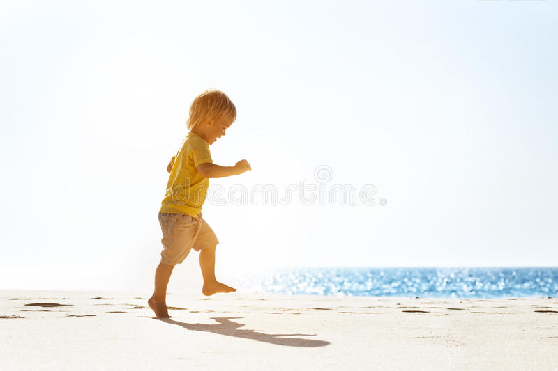 Happy baby walking at lonely beach stock photography