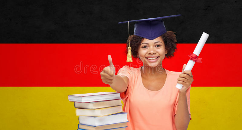 Happy bachelor girl with diploma showing thumbs up. Education, school, graduation, gesture and people concept - happy smiling african american student girl in royalty free stock photo