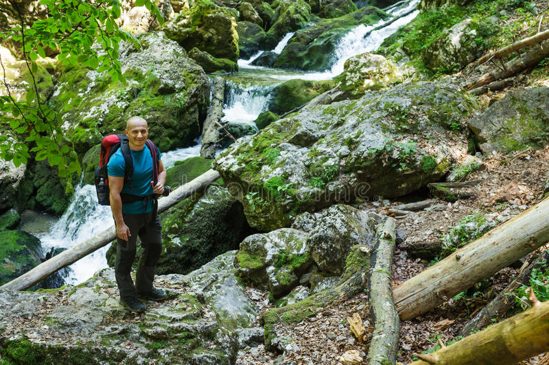 Happy backpacker with camera. Happy tourist with camera and backpack on a trail near the river royalty free stock image