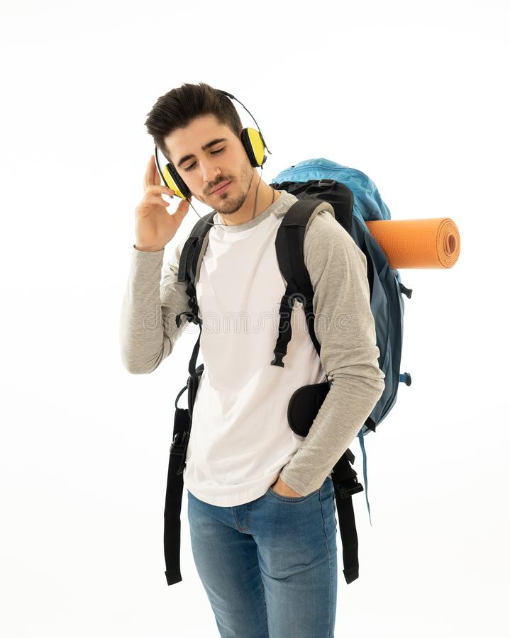 Happy backpacker young man in headphones listening to music and dancing isolated on white stock photo