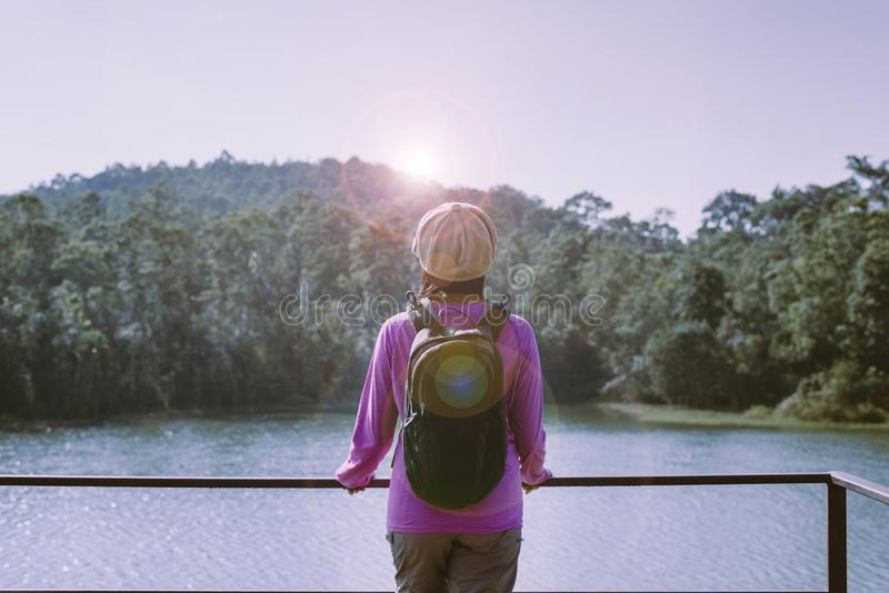Happy backpacking woman standing and looking beautiful view at nature,Back view royalty free stock photography