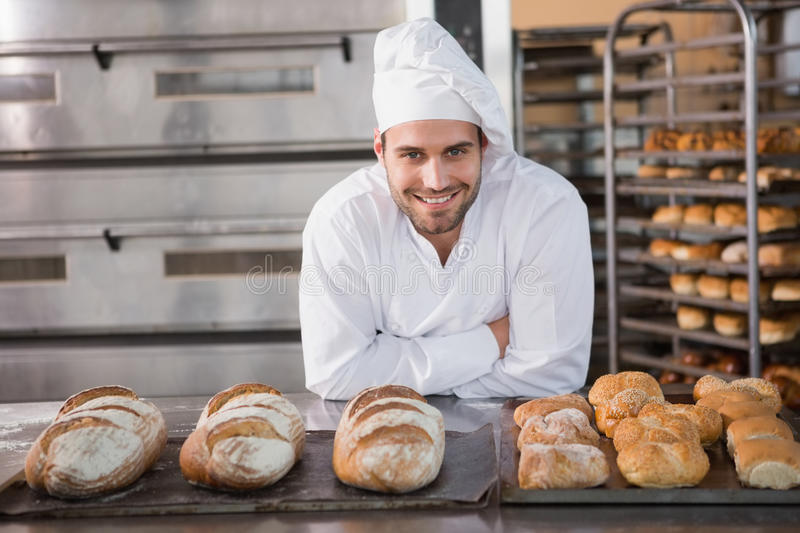 Happy baker standing near tray with bread royalty free stock photography