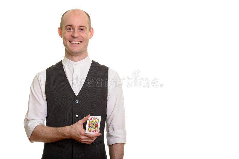 Happy bald Caucasian magician man smiling and bending Jack of Di royalty free stock photography