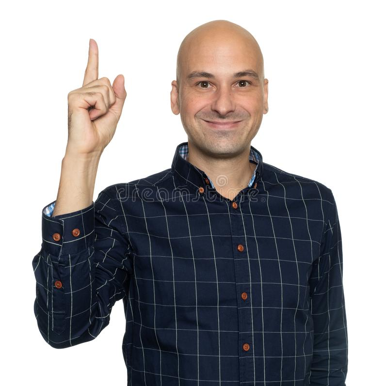Happy bald man pointing his finger up. Isolated stock image