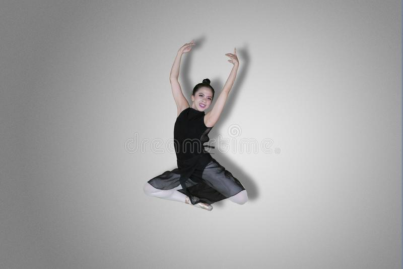 Happy ballet dancer performs elegant jump stock image