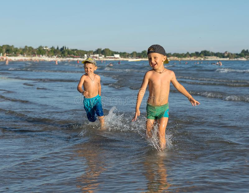 Happy barefoot family having fun - mother, son, together run with splashes by water pool along surf of sunset sea beach. Active royalty free stock photos