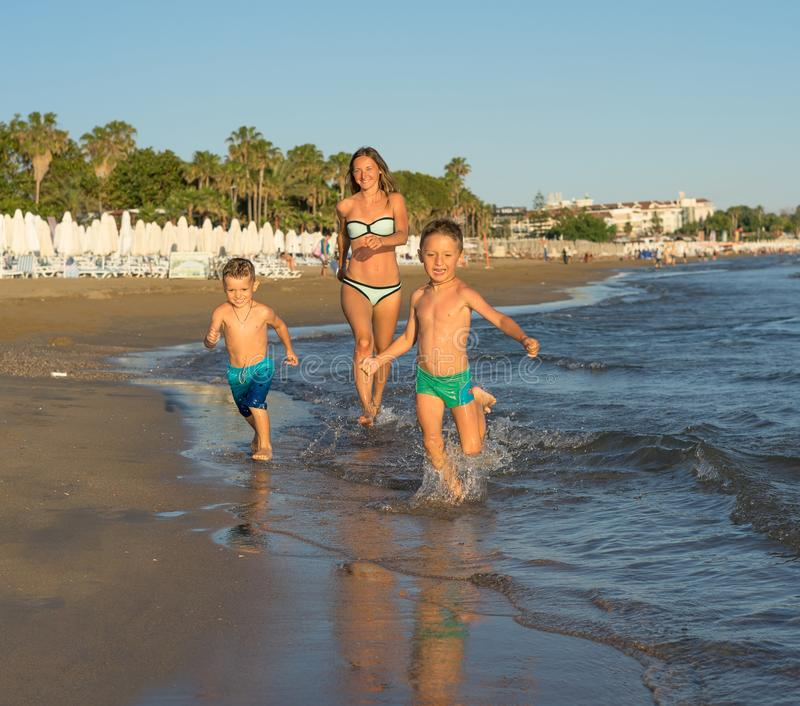 Happy barefoot family having fun - mother, son, together run with splashes by water pool along surf of sunset sea beach. Active stock images
