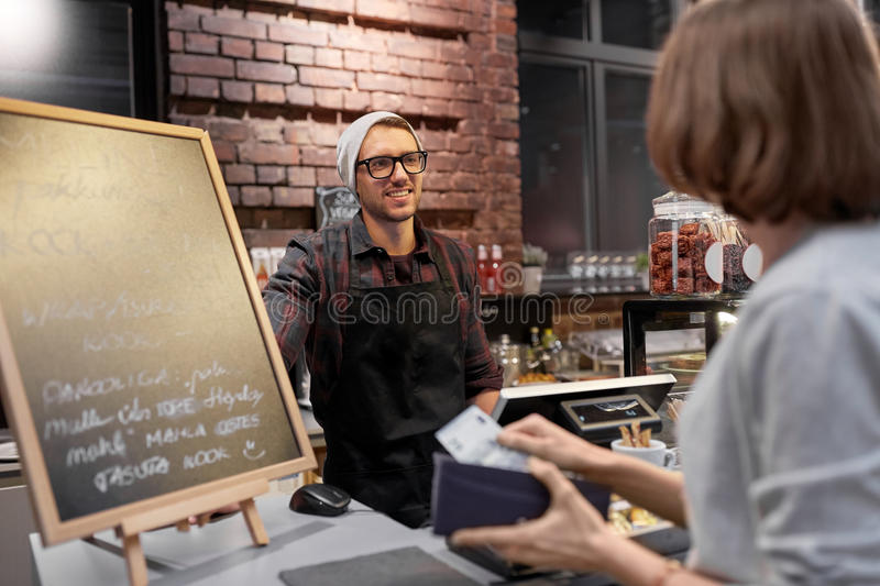 Happy barman and woman paying money at cafe stock images