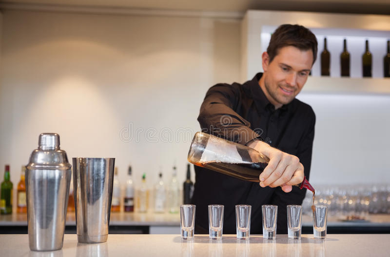 Happy bartender pouring cocktail into shot glasses royalty free stock photography