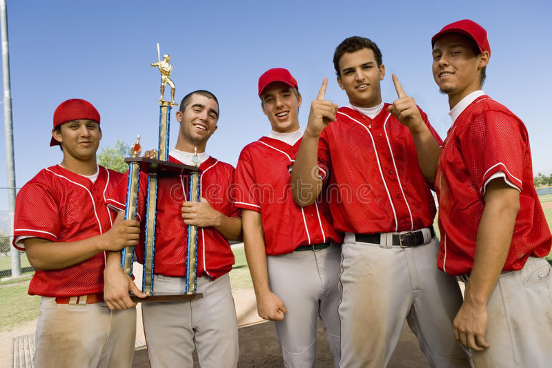 Happy Baseball Team With Trophy On Field stock photo