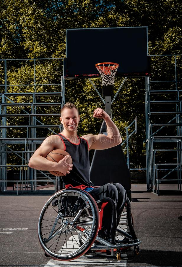 Happy basketball player in wheelchair pose with a ball on open gaming ground. Happy basketball player in a wheelchair pose with a ball on open gaming ground royalty free stock photo