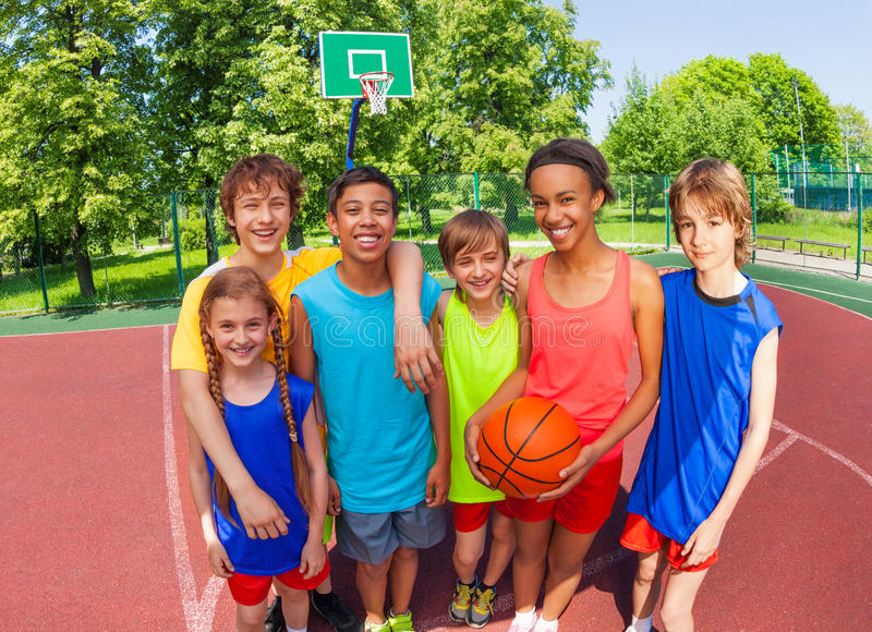 Happy basketball team stand in hug after game. Happy basketball team stand in hug close after game outside during sunny summer day royalty free stock image