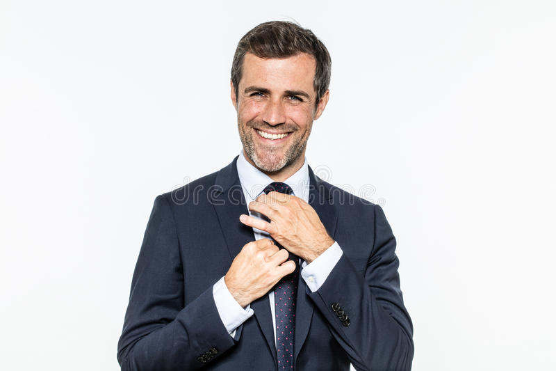 Happy bearded businessman fixing his dandy tie with elegant knot royalty free stock images
