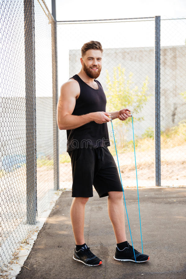 Happy bearded fitness man workout with jumping rope stock image