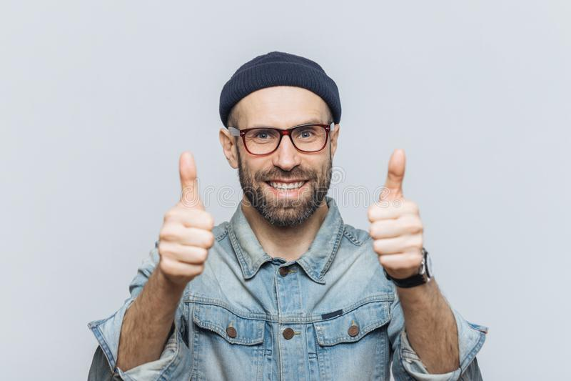 Happy bearded male model wears glasses, stylish hat and denim jacket, keeps thumbs raised, demonstrates approval and agreement wi royalty free stock photography