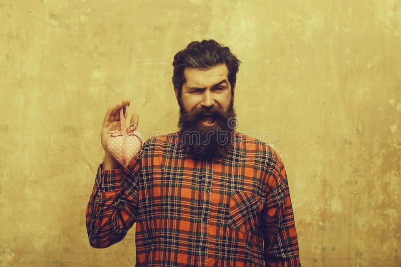 Happy bearded man with beard holds rosy textile heart. Happy bearded man, caucasian hipster, with long beard and moustache in plaid shirt holds rosy textile stock images