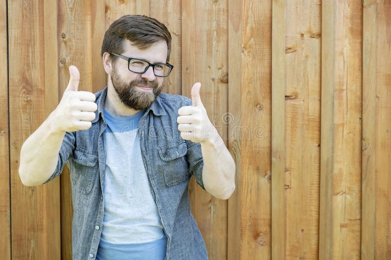A happy, bearded man in glasses gestures show thumbs up on two hands and looks into the camera, against the background of an old stock image