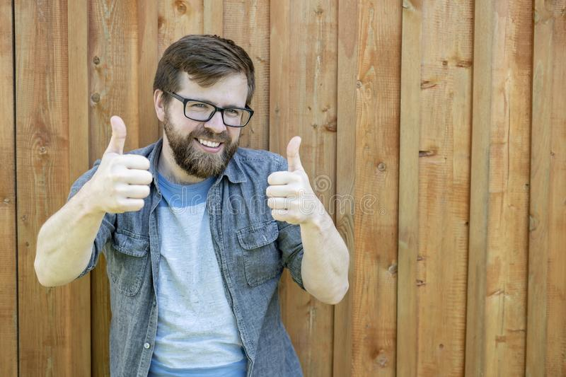 A happy, bearded man in glasses gestures show thumbs up on two hands and smiling looks into the camera, against the background of stock image