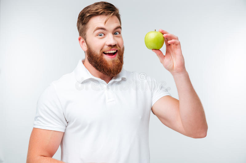 Happy bearded man holding green apple and looking at camera stock photos