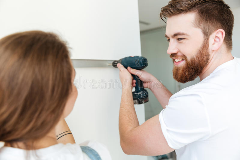 Happy bearded man looking at his woman. Happy bearded men looking at his women while she helping him royalty free stock photos