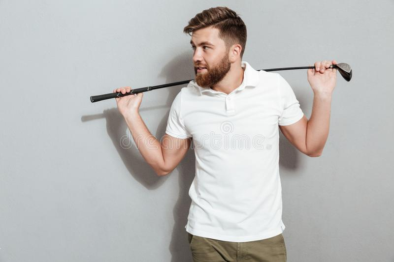 Happy bearded man posing with club and looking away royalty free stock image