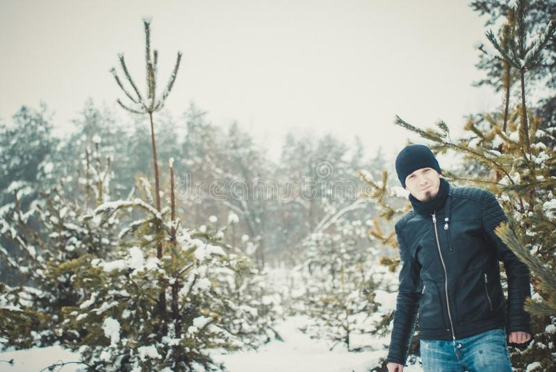 Happy bearded young man standing in wintertime outdoors. Happy bearded man standing in wintertime outdoors stock photos