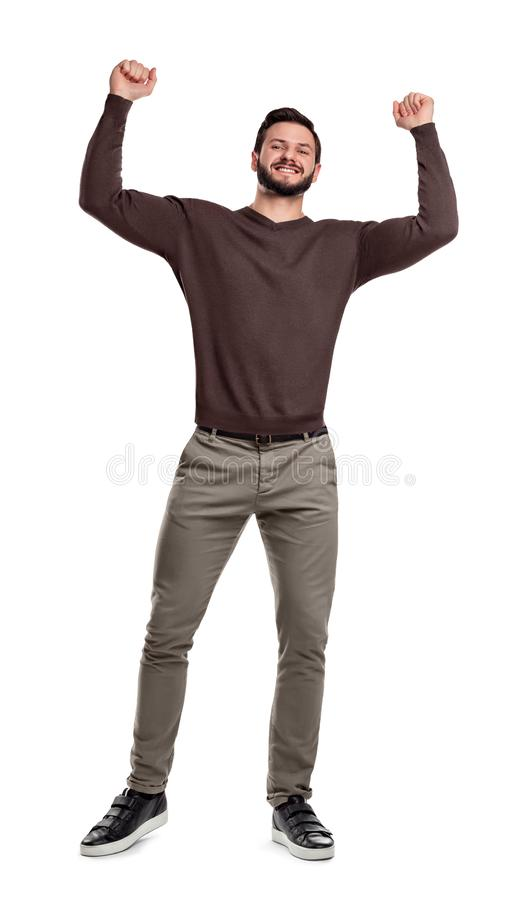 A happy bearded man stands in casual wear smiling and holding arms up in victory in tight fists. royalty free stock image