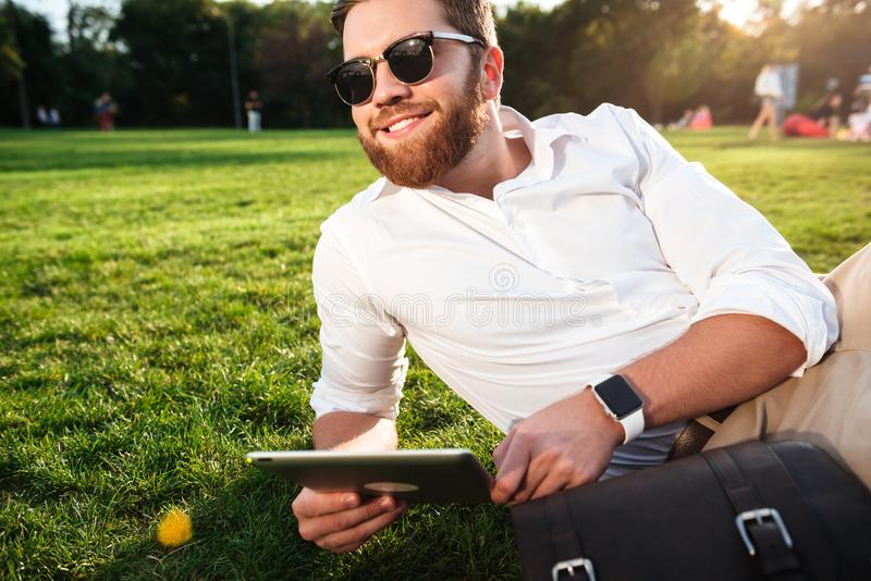 Happy bearded man in sunglasses lying on grass outdoors royalty free stock images