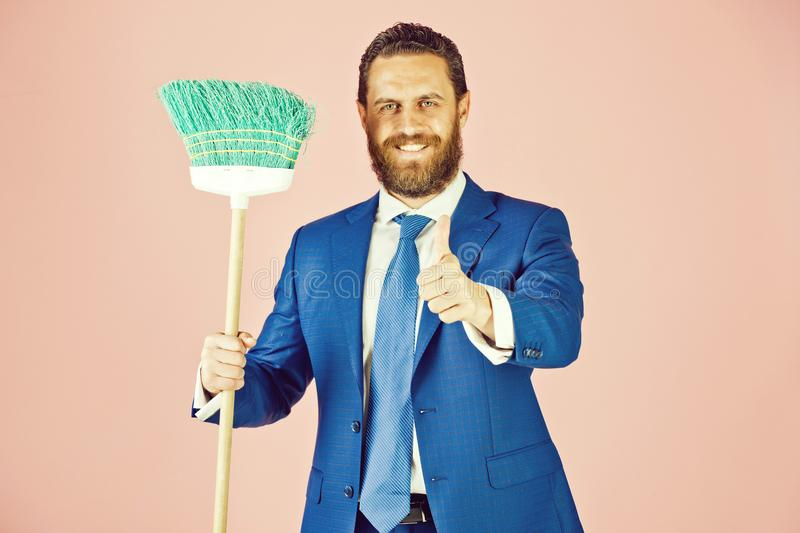 Happy bearded man with thumb up, broom in business outfit stock photography