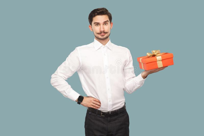 Happy bearded man in white shirt standing with hand on waist holding red gift box, looking at camera with satisfied face and royalty free stock photo