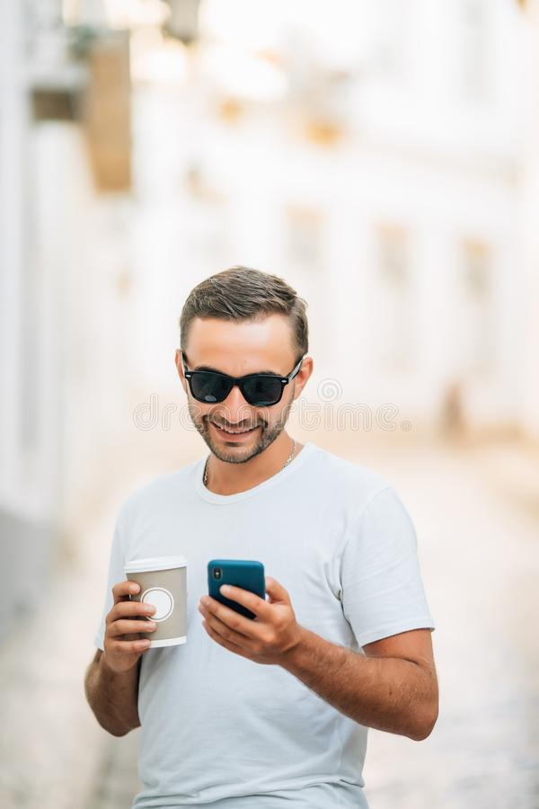 Happy bearded tourist with coffee to go in hand walking in urban setting of architectural city and smiling at camera. Positive you royalty free stock photos