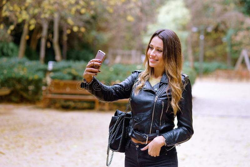 Happy beatiful woman taking selfie in park with leather jacket. Happy beatiful woman taking selfie in park royalty free stock photos