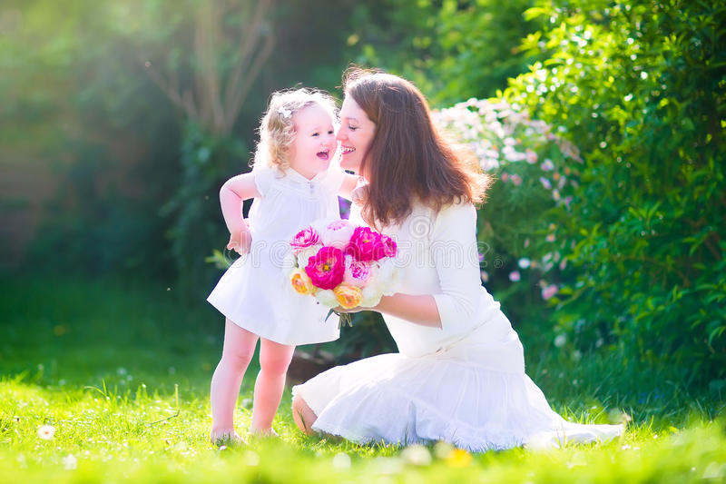 Happy beauiful mother and her daughter in garden. Beautiful young mother nd her adorable little daughter, cute little curly girl in a white dress, playing in the stock photography