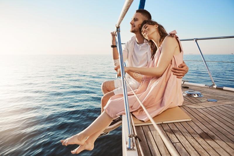 Happy beautiful adult couple sitting on side of yacht, watching at seaside and hugging while on vacation. Tan might fade stock photo