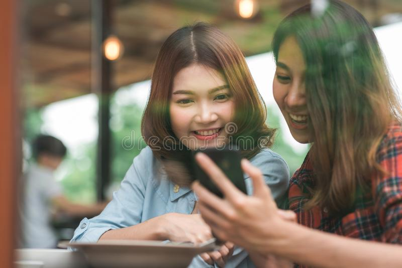 Happy beautiful Asian friends women blogger using smartphone photo and making food vlog video. stock image