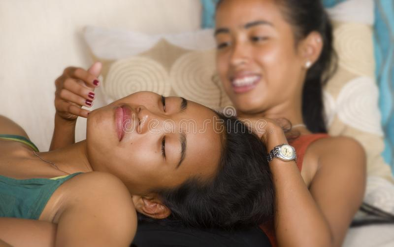Happy beautiful Asian gay girlfriends couple laughing cheerful together having fun at home sofa couch cuddling and enjoying in wom. En friendship or homosexual royalty free stock photography