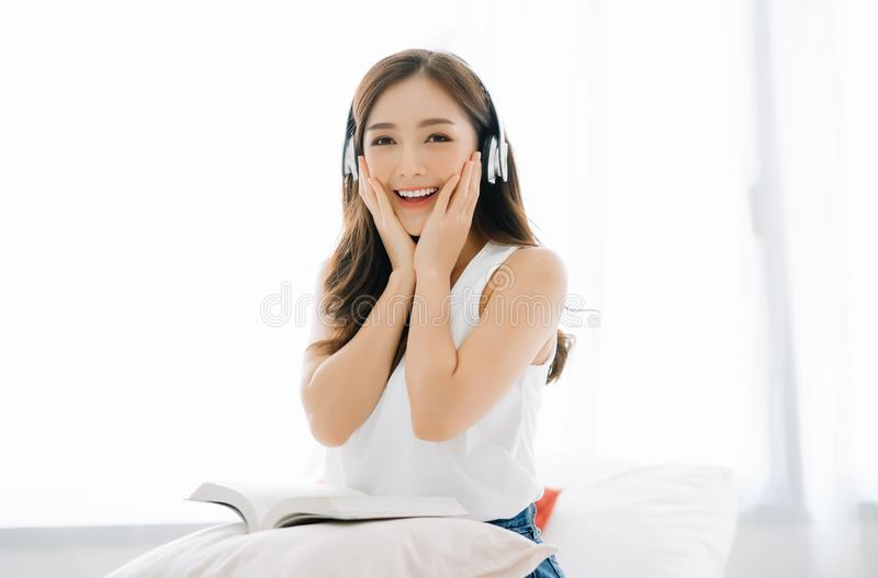 Happy beautiful Asian girl joyful listening to music using wireless earphones and holding her cheeks with a laugh looking to stock photography