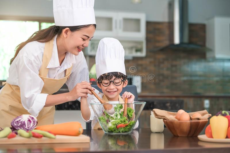 Happy beautiful Asian woman and cute little boy with eyeglasses prepare to cooking in kitchen at home. People lifestyles and stock image